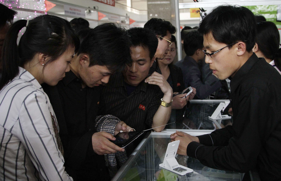 Photo - FILE - In this May 15, 2013 file photo, young North Koreans take a closer look at the Samjiyon tablet computer produced for the North Korean market for sale at the 16th Pyongyang Spring International Trade Fair in Pyongyang. North Korea is literally off the charts regarding Internet freedoms. There essentially aren't any. But the country is increasingly online. Though it deliberately and meticulously keeps its people isolated and in the dark about the outside world, it knows it must enter the information age to survive in the global economy. (AP Photo/Jon Chol Jin, File)