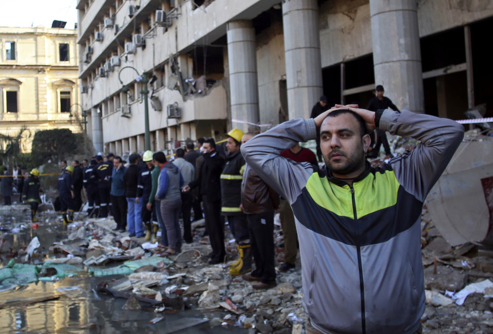 An Egyptian man stands in rubble after an explosion at the Egyptian police headquarters in downtown Cairo, Friday, Jan. 24, 2014. Three bombings hit high-profile areas around Cairo on Friday, including a suicide car bomber who struck the city's police headquarters, killing several people in the first major attack on the Egyptian capital as insurgents step up a campaign of violence following the ouster of the Islamist president. (AP Photo/Khalil Hamra)