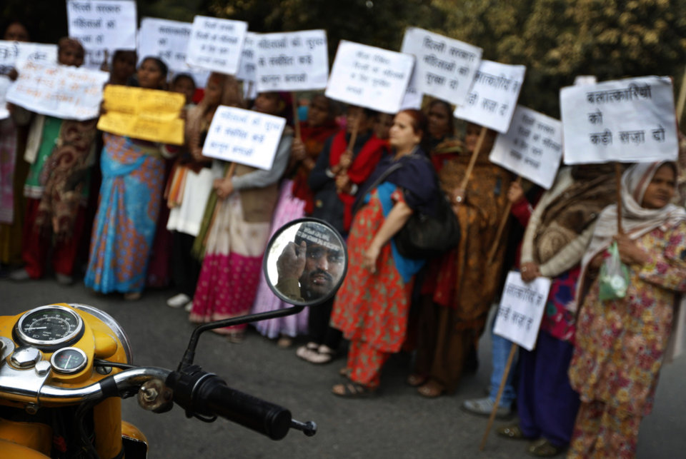 A policeman is reflected in the mirror of his motor bike as he keeps an eye on women who gathered to mourn the death of a gang rape victim in New Delhi, India, Saturday, Dec. 29, 2012. Shocked Indians on Saturday were mourning the death of the woman who was gang-raped and beaten on a bus in New Delhi nearly two weeks ago in an ordeal that galvanized people to demand greater protection for women from sexual violence. (AP Photo/ Saurabh Das)