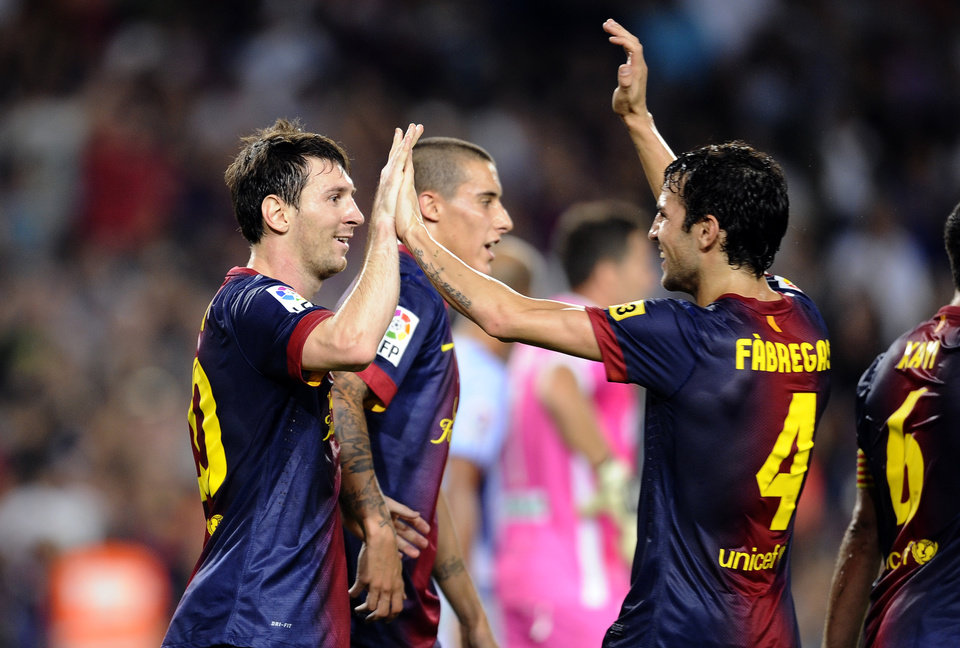 Photo -   FC Barcelona's Lionel Messi from Argentina, left, reacts after scoring with his teammate Cesc Fabregas, right, against Granada during a Spanish La Liga soccer match at the Camp Nou stadium in Barcelona, Spain, Saturday, Sept. 22, 2012. (AP Photo/Manu Fernandez)