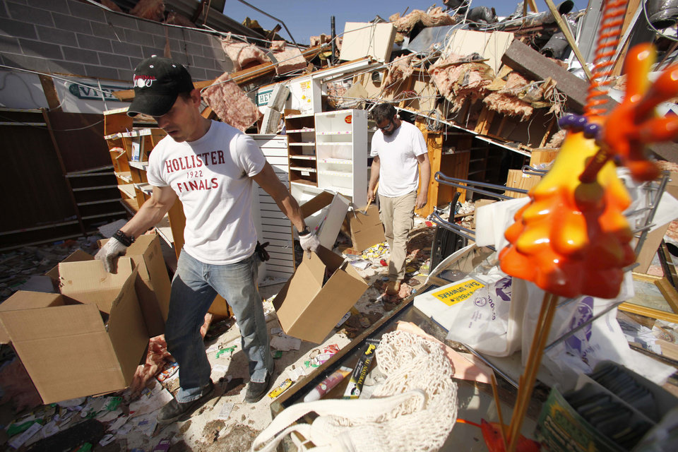 Tim Thress, left, of Branson, and Wake Williams of Omaha, Ark., help carry merchandise out of a friend's storm-damaged store in Branson, Mo., Wednesday, Feb. 29, 2012. Powerful storms that produced reports of multiple tornadoes and killed at least nine people elsewhere in the Midwest tore through the music resort town early this morning, injuring more than three dozen people. (AP Photo/Mark Schiefelbein) ORG XMIT: MOMS118