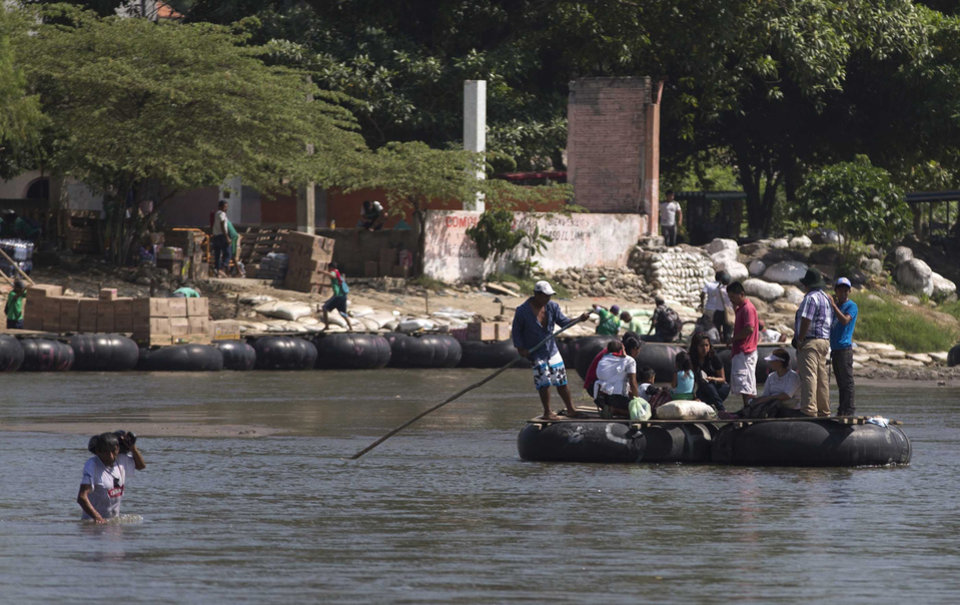 Photo - In this Friday, July 11, 2014 photo, people cross the Suchiate river that separates, Tecun Uman, Guatemala, from Ciudad Hidalgo, Mexico, aboard makeshift rafts made from truck inner tubes lashed to wooden boards. Scores of Central American migrants pay a modest fee crossing the river on these improvised rafts. (AP Photo/Eduardo Verdugo)
