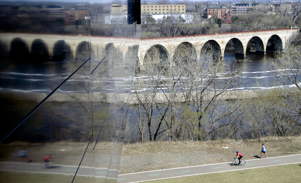 Photo - FILE - In this April 20, 2007 file photo, The Stone Arch Bridge over the Mississippi River is reflected in the