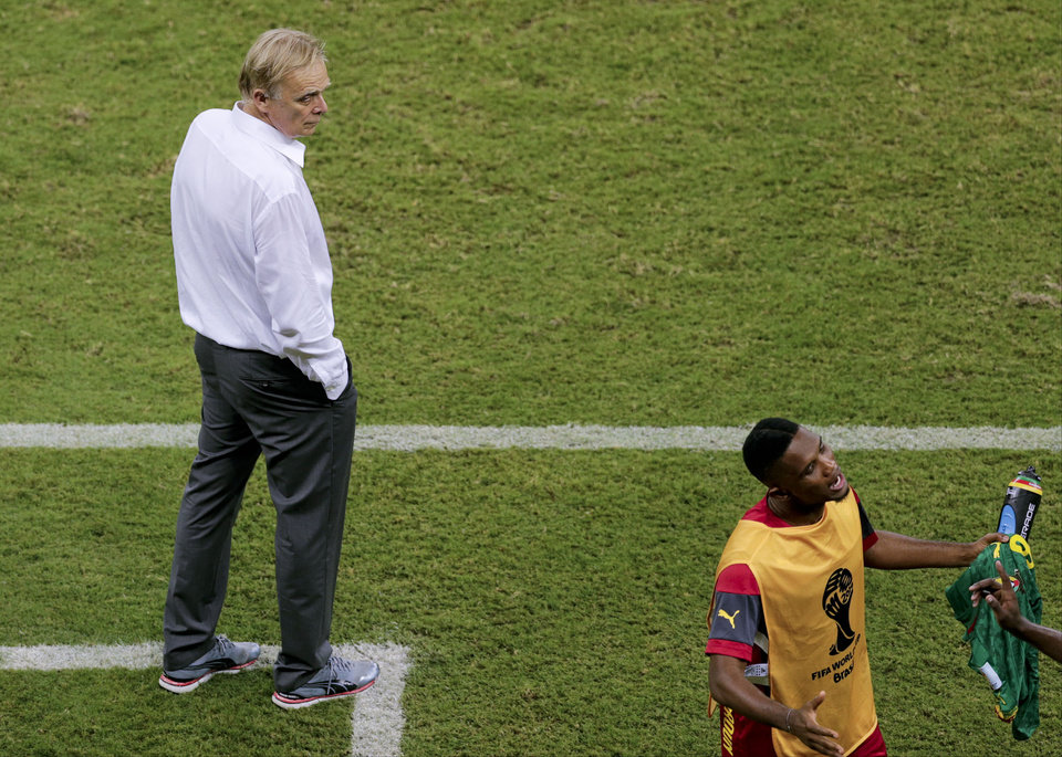 Photo - Cameroon's coach Volker Finke, left, looks to arguing players during the group A World Cup soccer match between Cameroon and Croatia at the Arena da Amazonia in Manaus, Brazil, Wednesday, June 18, 2014. (AP Photo/Fernando Llano)