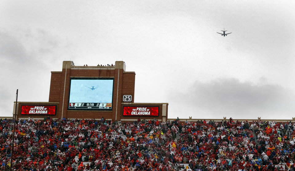 Photo - Members of the Winchester family watch as a commercial airliner performs a flyover  before the Bedlam college football game between the Oklahoma Sooners (OU) and the Oklahoma State Cowboys (OSU) at Gaylord Family - Oklahoma Memorial Stadium in Norman, Okla., Saturday, Dec. 3, 2016. Photo by Steve Sisney, The Oklahoman