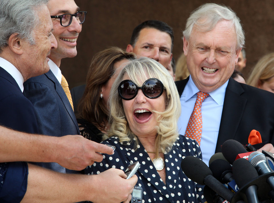 Photo - FILE - In this July 28, 2014, file photo, with her attorney Pierce O'Donnell, right, Shelly Sterling, center, talks to reporters after a judge ruled in her favor and against her estranged husband, Los Angeles Clippers owner Donald Sterling, in his attempt to block the $2 billion sale of the NBA basketball team, outside Los Angeles Superior Court. Steve Ballmer is officially the new owner of the Clippers. The team says the sale closed Tuesday, Aug. 12, 2014,  after a California court confirmed the authority of Shelly Sterling, on behalf of the Sterling Family Trust, to sell the franchise. (AP Photo/Nick Ut, File)