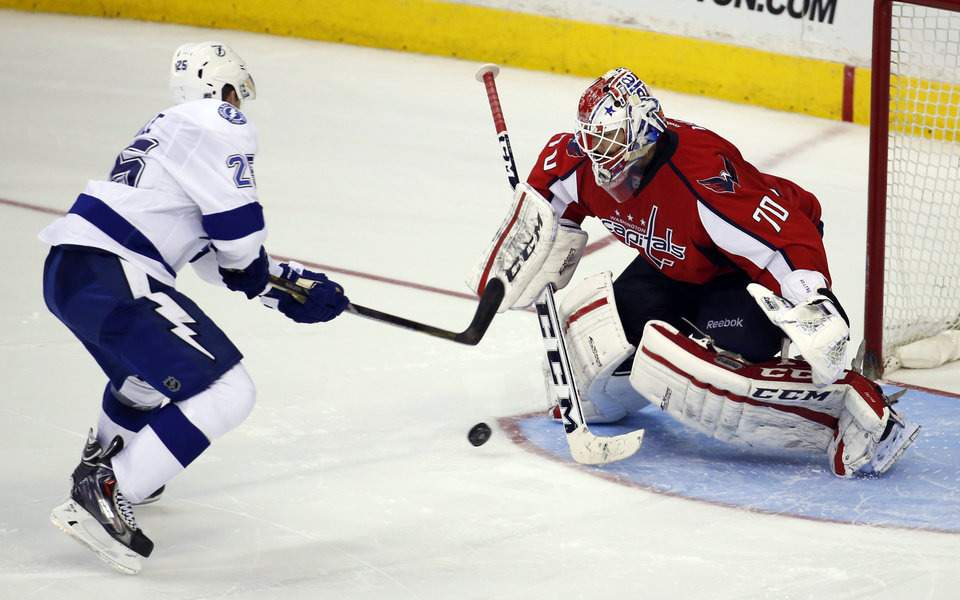 Photo - Tampa Bay Lightning defenseman Matt Carle (25) shoots the game-winning goal past Washington Capitals goalie Braden Holtby (70) in the shootout portion of an NHL hockey game on Sunday, April 13, 2014, in Washington. The Lightning won 1-0. (AP Photo/Alex Brandon)