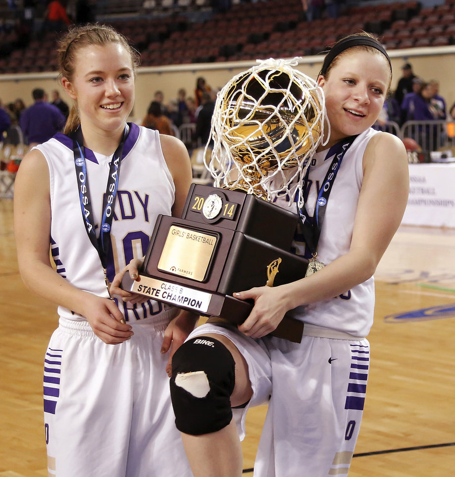 Photo - Okarche seniors Laci Friesen, left, and Madi Grellner carry the gold ball off the court after team photos were taken with the championship trophy  at the end of the Class B girls high school basketball championship game in the Jim Norick Arena at State Fair Park on  Saturday, March 8, 2014.  Okarche defeated Red Oak,   66-41. Photo by Jim Beckel, The Oklahoman