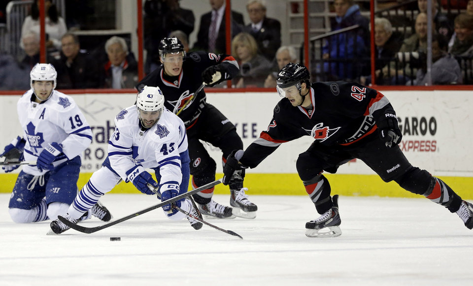 Photo - Carolina Hurricanes' Brett Sutter (42) and Alexander Semin, rear, of Russia, chase the puck against Toronto Maple Leafs' Nazem Kadri (43) and Joffrey Lupul (19) during the first period of an NHL hockey game in Raleigh, N.C., Thursday, Jan. 9, 2014. (AP Photo/Gerry Broome)