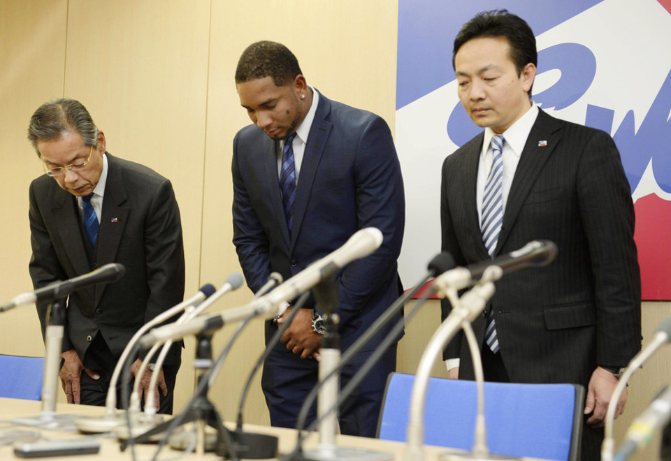 Photo - Yakult Swallows slugger Wladimir Balentien, center, bows during a press conference in Tokyo Wednesday, Jan. 29, 2014. Balentien has apologized to his fans, several days after pleading not guilty to domestic violence charges in Florida. As is the custom in Japan, Balentien bowed deeply and then apologized Wednesday to his fans and teammates for the actions that led to his arrest on Jan. 13. (AP Photo/Kyodo News) JAPAN OUT, MANDATORY CREDIT