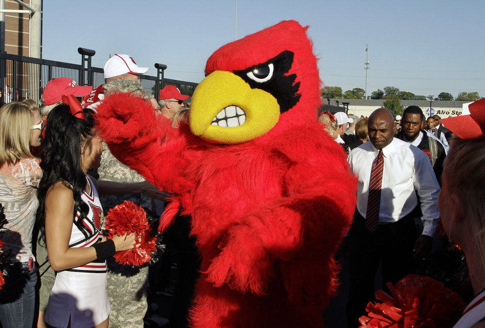 Photo - File-This Oct. 10, 2013, file photo shows the Cardinal Bird mascot leading then football coach Charlie Strong, right, and the team into the stadium before Louisville's NCAA college football game against Rutgers in Louisville, Ky.  The musical chairs of conference realignment returns this this week, with more major colleges taking new seats. On Tuesday, July 1, 2014, 12 FBS teams officially switch places, including Louisville in the Atlantic Coast Conference and Maryland and Rutgers in the Big Ten. (AP Photo/Garry Jones, File)