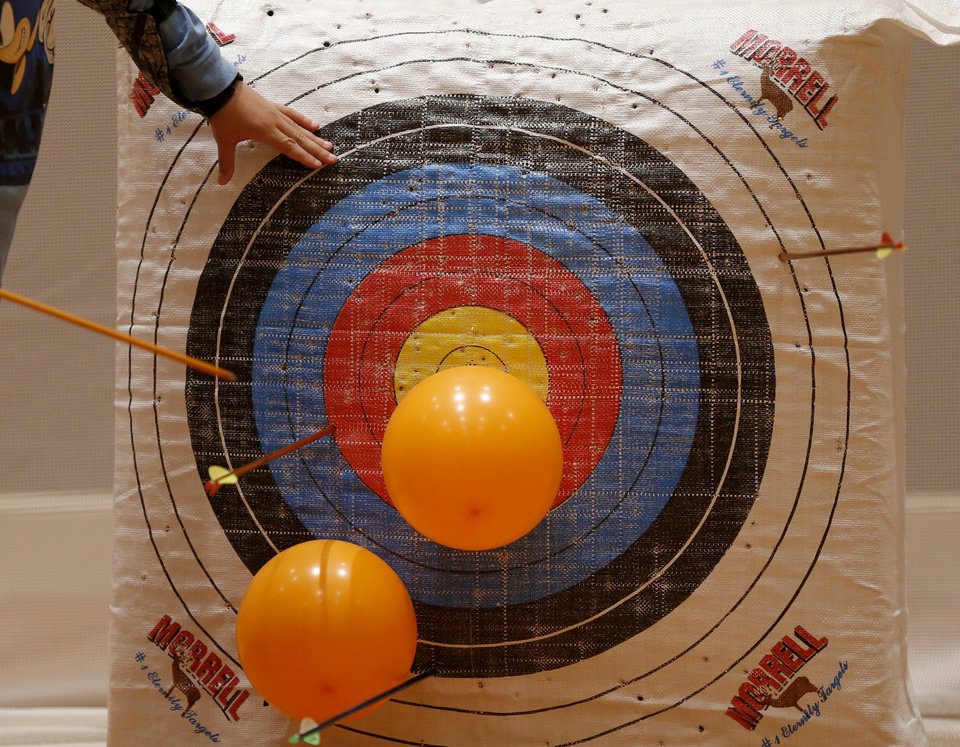 Photo - A student pulls out arrows from a target during an after-school archery class in Edmond.