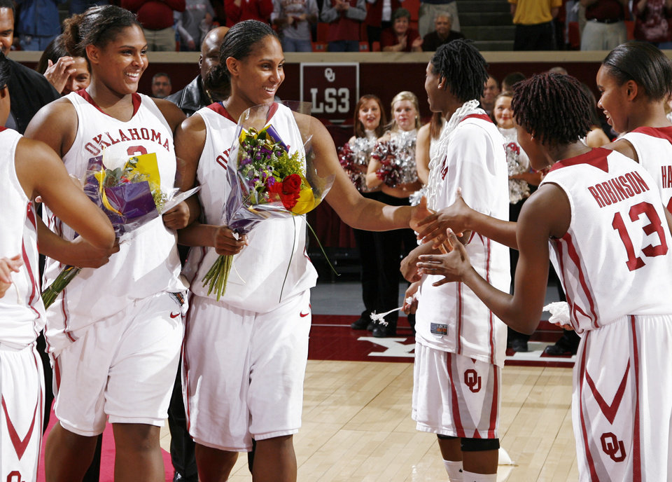 Photo - Courtney Paris, left, and Ashley Paris, each holding flowers, greet Danielle Robinson and Jasmine Hartman as they are honored as part of senior night after the women's college basketball game between Texas Tech and the University of Oklahoma at the Lloyd Noble Center in Norman, Okla., Wednesday, March 4, 2009. OU beat Texas Tech, 61-49. BY NATE BILLINGS, THE OKLAHOMAN ORG XMIT: KOD