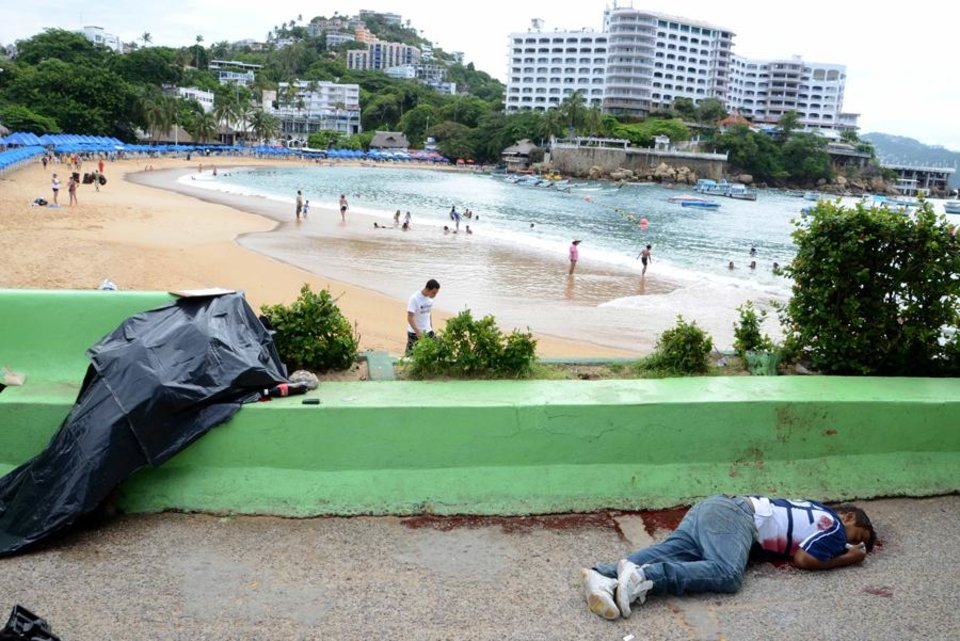 Photo -  EDITORS NOTE GRAPHIC CONTENT - The bodies of two men shot dead next to the Caleta beach,  background,  lie, one of them covered,  in the Pacific resort city of Acapulco, Mexico, Tuesday Aug. 16, 2011. The city of Acapulco has been hit by violence as drug gangs continue to battle for control of the region. (AP Photo/Bernandino Hernandez)