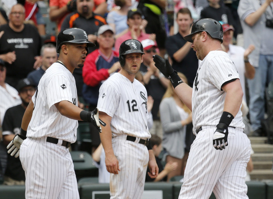 Photo - Chicago White Sox's Jose Abreu, left, and Conor Gillaspie (12) greet Adam Dunn at home after the trio scored on Dunn's home run off San Francisco Giants starting pitcher Tim Hudson, during the fifth inning of an interleague baseball game Wednesday, June 18, 2014, in Chicago. (AP Photo/Charles Rex Arbogast)