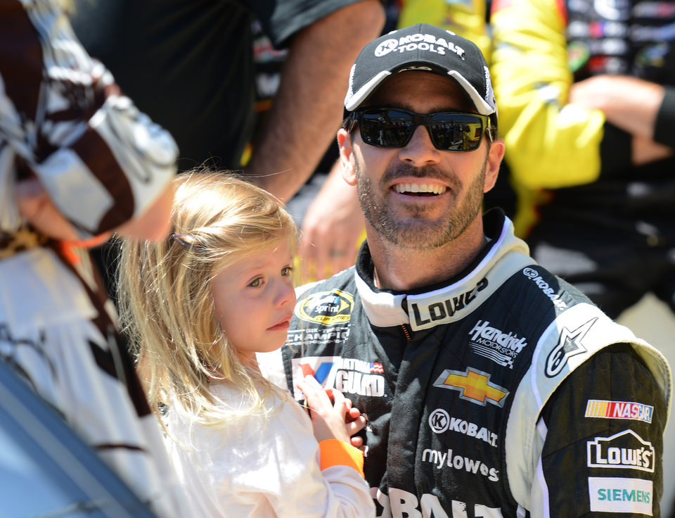 Photo - Jimmie Johnson holds his daughter Genevieve, left, before driving in the NASCAR Sprint Cup series auto race at Dover International Speedway, Sunday, June 1, 2014, in Dover, Del. (AP Photo/Molly Riley)