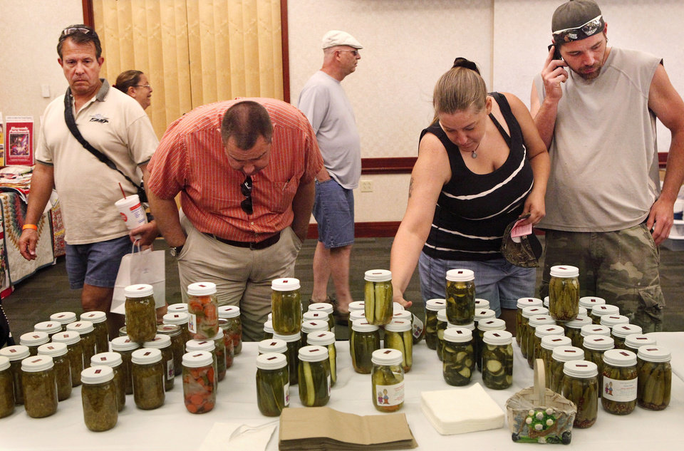 Visitors check out some of the items displayed at a table featuring products from A & K Enterprises at the Made in Oklahoma Festival held inside and on the grounds of the Reed Conference Center at the Sheraton Midwest City Hotel Saturday afternoon, May, 19, 2012.  Their business includes salsas, jams and jellies, pickled okra, peanut brittle and fudge. Photo by Jim Beckel, The Oklahoman