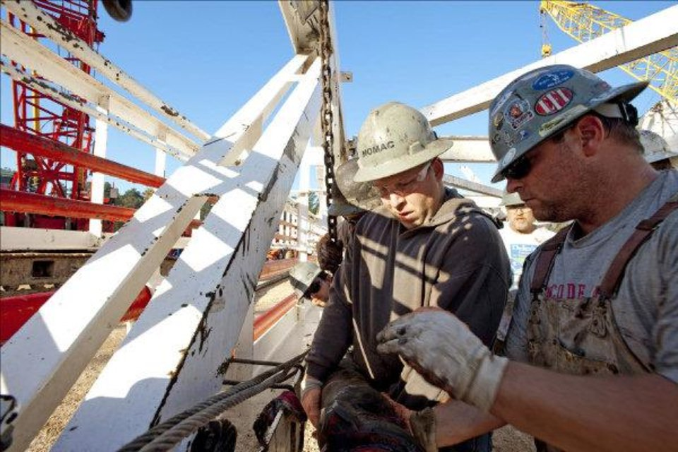 Workers with Chesapeake Energy Corp. subsidiary Nomac Drilling work on a rig near Shreveport, La., in 2009. - provided