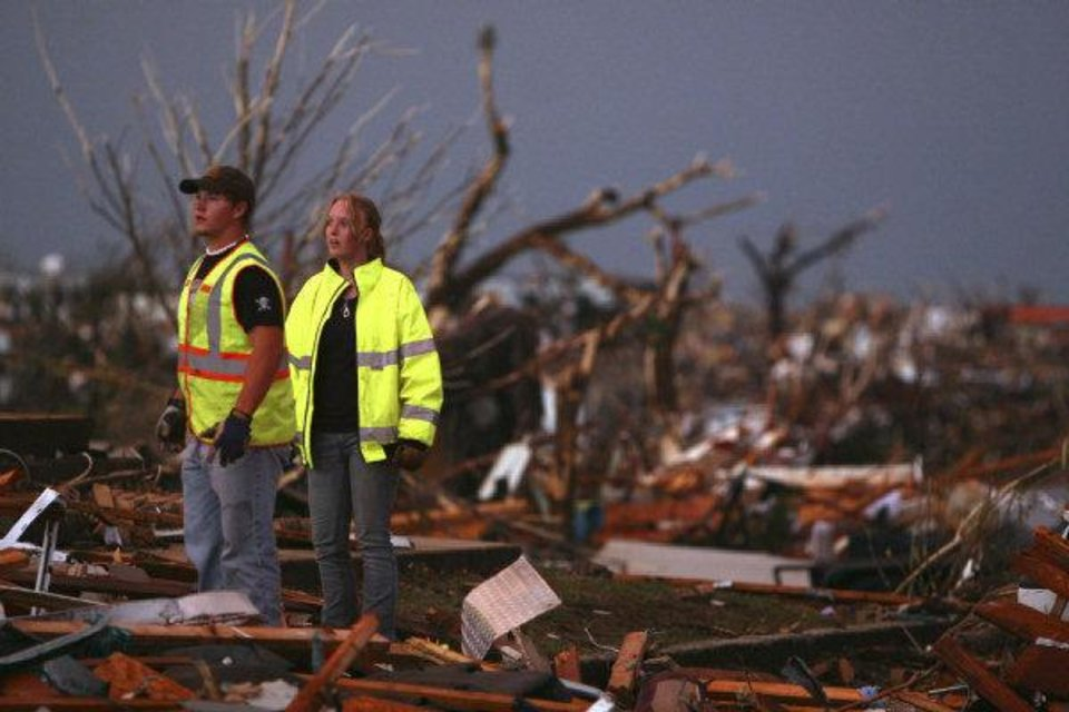 Photo - William Jackson, left, and Ashley Martin, volunteer firefighters from Oklahoma, survey the wreckage of destroyed homes in Joplin, Mo., Sunday, May 22, 2011. A large tornado moved through much of the city, damaging a hospital and hundreds of homes and businesses. (AP Photo/Mark Schiefelbein) ORG XMIT: MOMS104