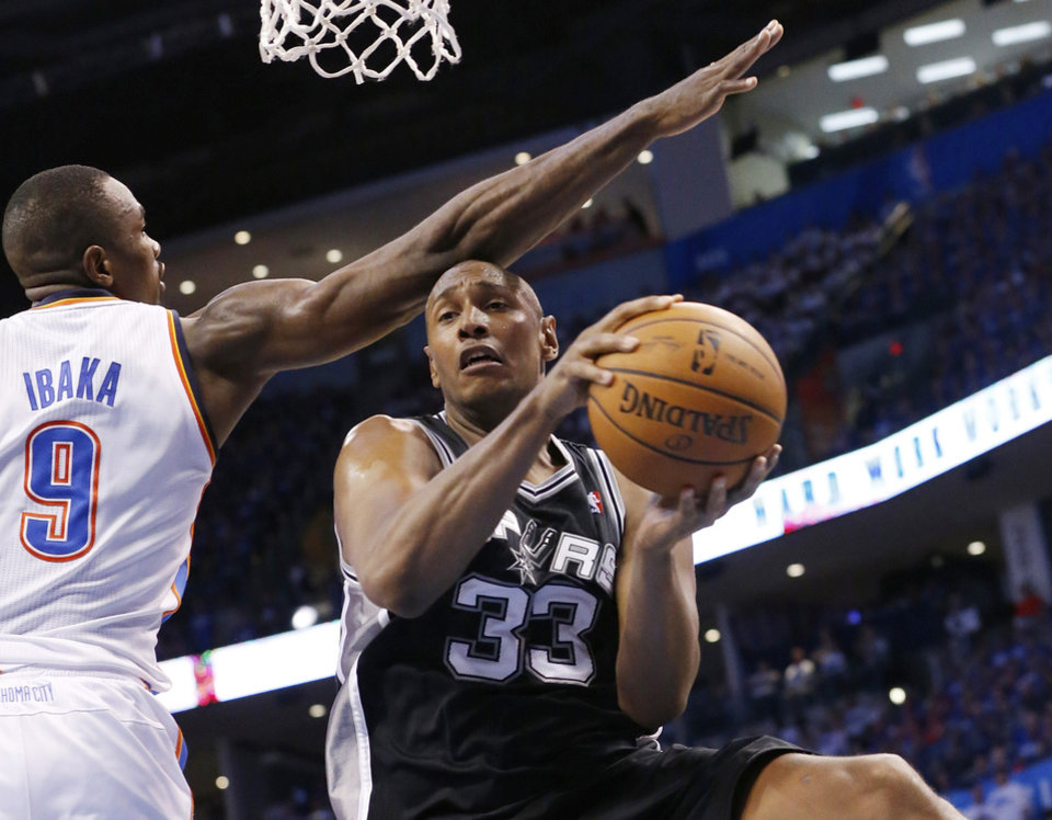 Photo - San Antonio Spurs forward Boris Diaw (33) drives under the basket past Oklahoma City Thunder forward Serge Ibaka (9) in the third quarter of Game 4 of the Western Conference finals NBA basketball playoff series in Oklahoma City, Tuesday, May 27, 2014. Oklahoma City won 105-92. (AP Photo/Sue Ogrocki)
