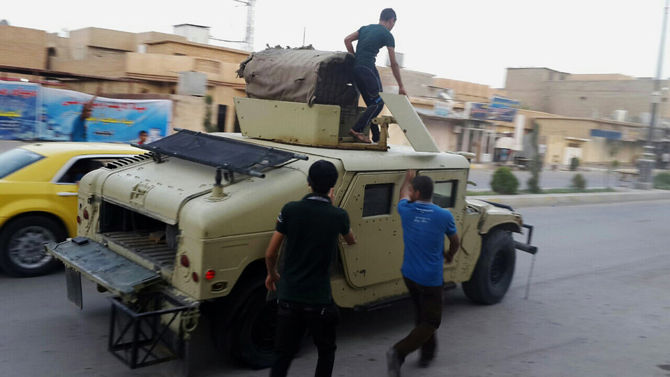 Photo - Teenagers ride on an armored vehicle belonging to the Iraqi army in Tikrit, 80 miles (130 kilometers) north of Baghdad, Iraq, Wednesday, June 11, 2014. Al-Qaida-inspired militants seized effective control Wednesday of Saddam Hussein's hometown of Tikrit, expanding their offensive closer to the Iraqi capital as soldiers and security forces abandoned their posts following clashes with the insurgents. (AP Photo)