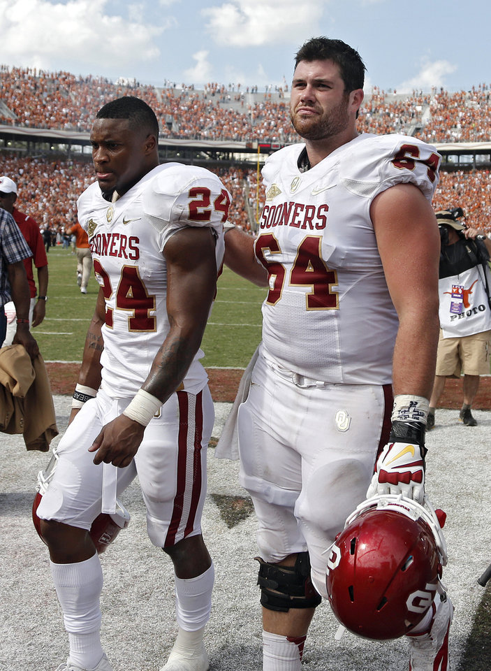 OU\'s Brennan Clay (24) and Gabe Ikard (64) walk off the field after the 36-20 loss to Texas during the Red River Rivalry college football game between the University of Oklahoma Sooners (OU) and the University of Texas Longhorns (UT) at the Cotton Bowl Stadium in Dallas, Saturday, Oct. 12, 2013. Photo by Chris Landsberger, The Oklahoman