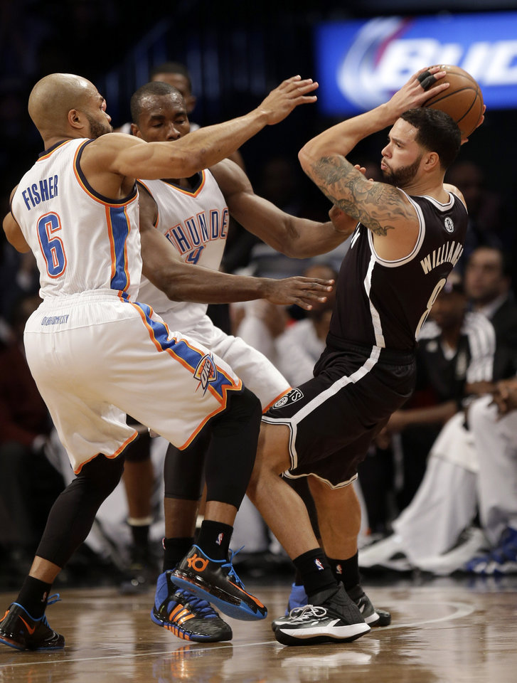 Brooklyn Nets' Deron Williams, right, is pressured by Oklahoma City Thunder's Derek Fisher, left, and Serge Ibaka during the first half of an NBA basketball game Friday, Jan. 31, 2014, in New York. (AP Photo/Seth Wenig)