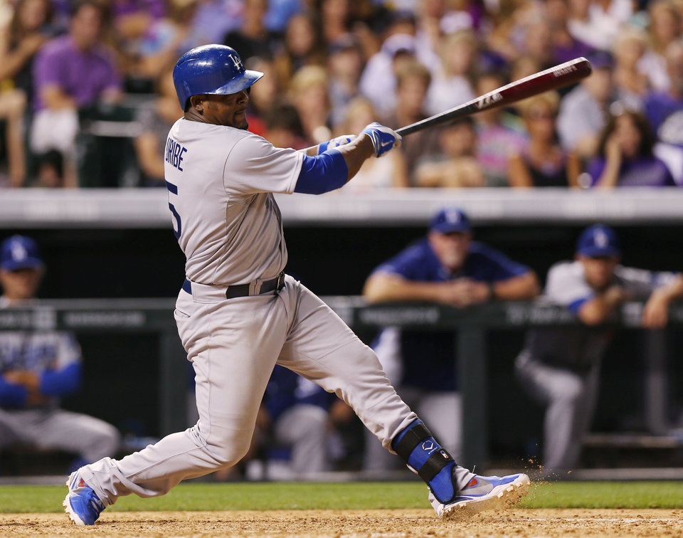 Photo - Los Angeles Dodgers' Juan Uribe follows through with his swing after hitting an RBI-single to drive in the go-ahead run against the Colorado Rockies in the ninth inning of the Dodgers' 3-2 victory in a baseball game in Denver,  Thursday, July 3, 2014. (AP Photo/David Zalubowski)