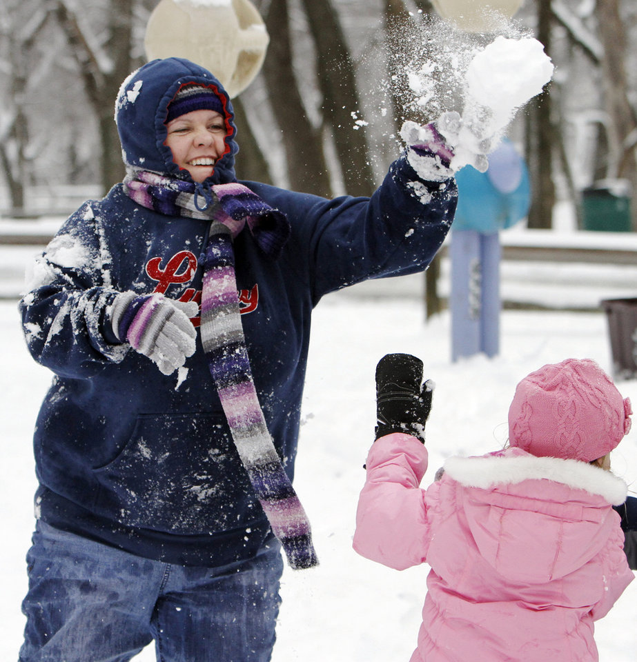 Photo - Dorothy Masters throws a snowball over the head of Summer Bennett, 4, at Hafer Park in Edmond, Okla., Saturday, January 30, 2010. Photo by Nate Billings, The Oklahoman