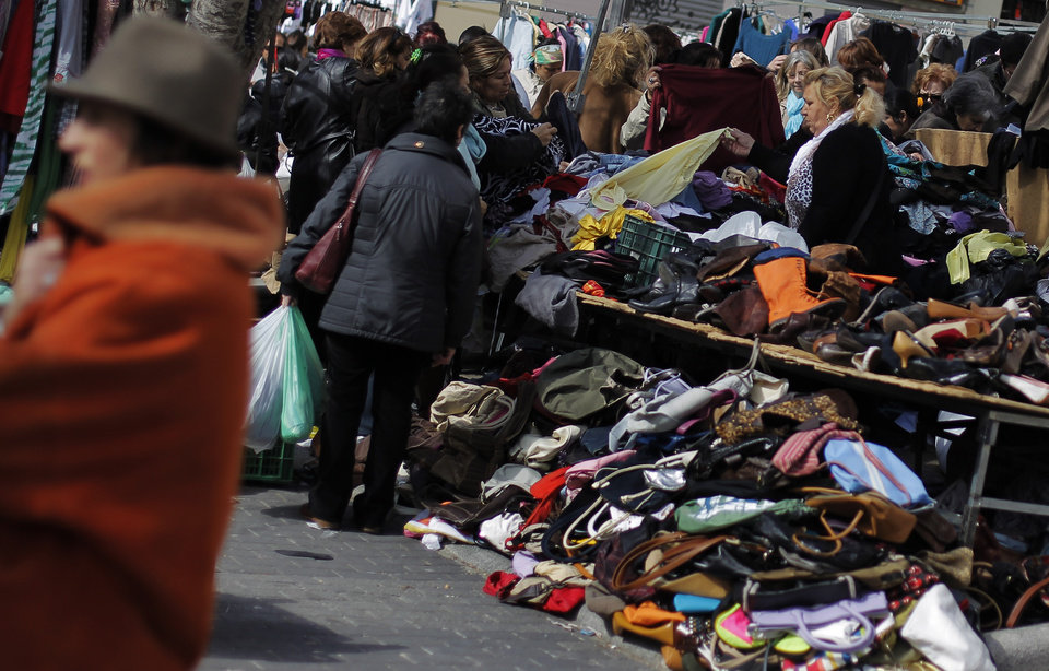 Photo - People look at second hand items for sale at a street market in Madrid, Sunday, March 3, 2013. Spain's Prime Minister Mariano Rajoy has conceded that the government just failed to reduce its budget deficit in 2012 to the level it promised European authorities. Rajoy said the deficit fell to 6.7 percent of the country's annual gross domestic product from 9 percent in 2011. (AP Photo/Andres Kudacki)