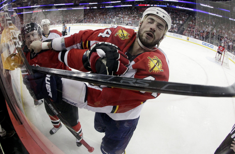 Photo -   New Jersey Devils' Ryan Carter, left, and Florida Panthers' Erik Gudbranson scuffle during the first period of Game 3 of a first-round NHL hockey Stanley Cup playoff series Tuesday, April 17, 2012, in Newark, N.J. (AP Photo/Julio Cortez)