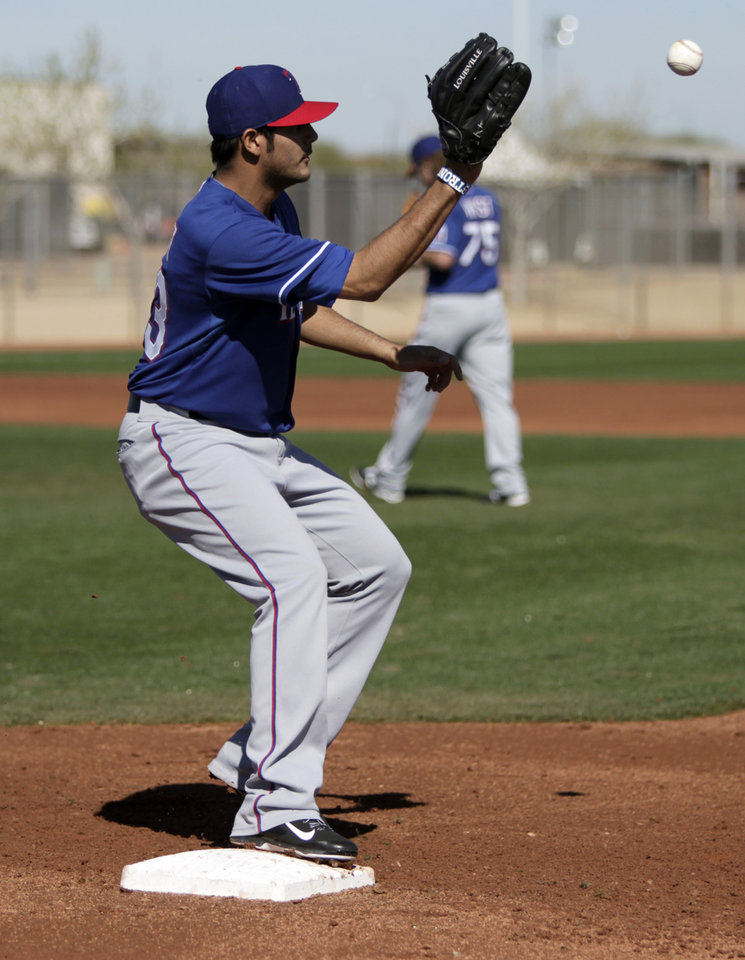 Photo - Texas Rangers' Martin Perez (33) reaches out for the throw as he covers first in fielding practice during spring training baseball practice, Monday, Feb. 17, 2014, in Surprise, Ariz. (AP Photo/Tony Gutierrez)