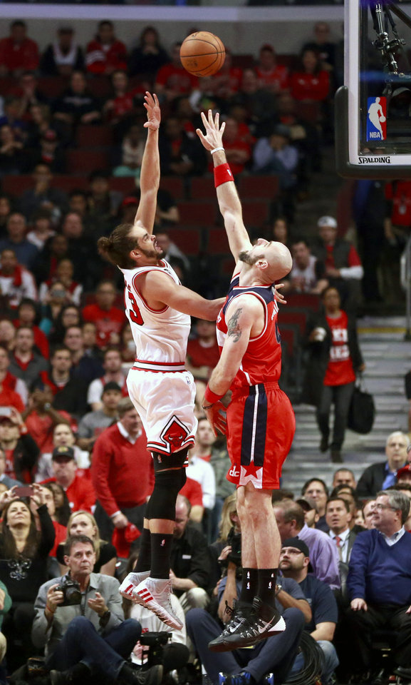 Photo - Chicago Bulls center Joakim Noah, left, shoots over Washington Wizards center Marcin Gortat during the first half of Game 5 in an opening-round NBA basketball playoff series Tuesday, April 29, 2014, in Chicago. (AP Photo/Charles Rex Arbogast)
