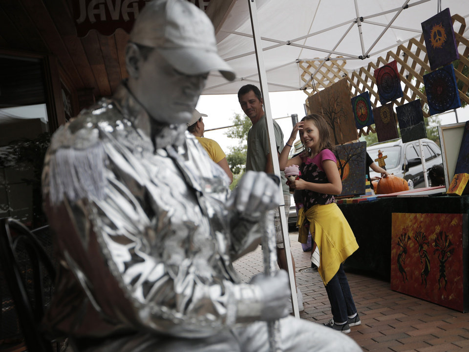 CHILD / CHILDREN / KIDS: Isabella Burnner, 10 of Edmond, walks by the Silver Man during the Downtown Edmond Fall Art Crawl in Edmond, Okla., Saturday, Sept. 29, 2012.  Photo by Garett Fisbeck, The Oklahoman
