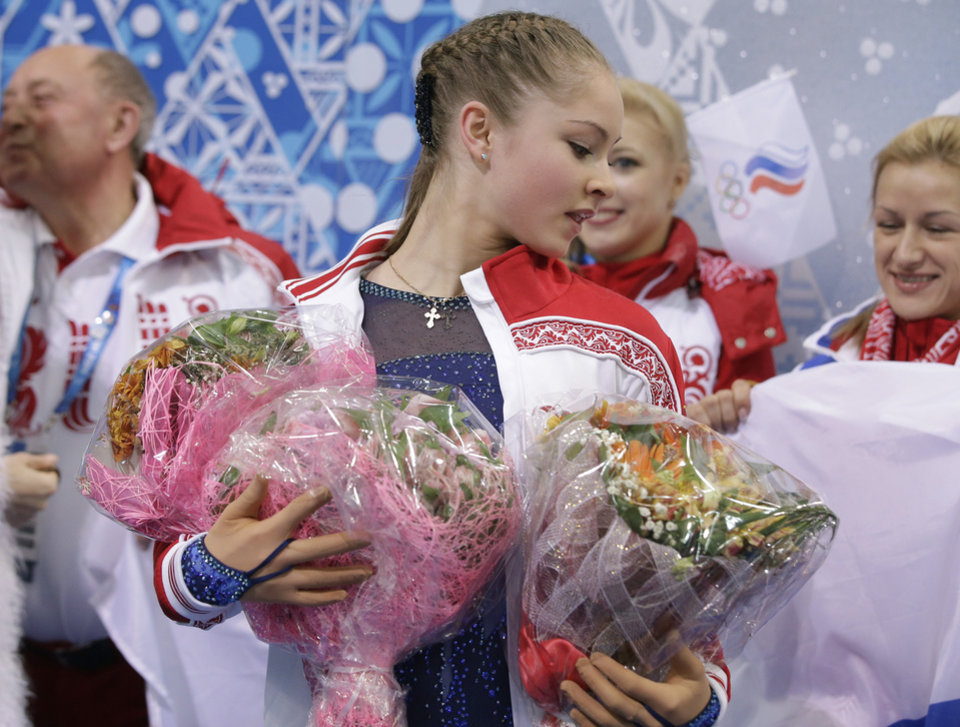 Photo - Yulia Lipnitskaya of Russia holds flowers given to her by spectators after competing in the women's team short program figure skating competition at the Iceberg Skating Palace during the 2014 Winter Olympics, Saturday, Feb. 8, 2014, in Sochi, Russia. (AP Photo/Darron Cummings, Pool)