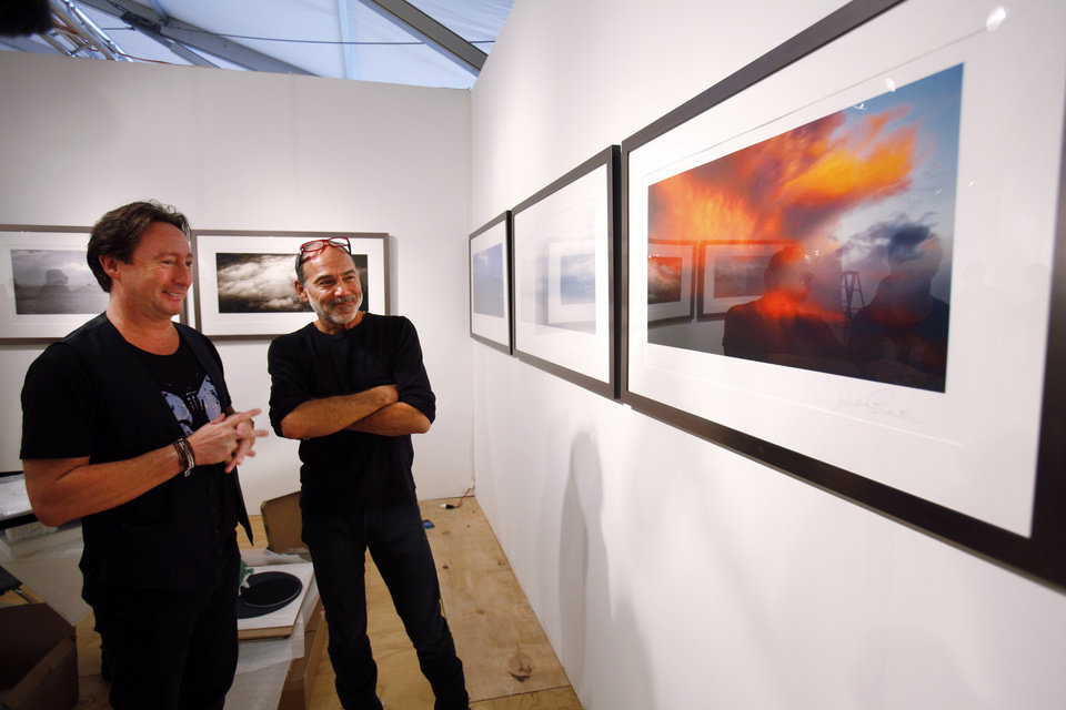 "Photo - Julian Lennon, son of the late Beatles legend John Lennon, left, and and his friend, celebrity photographer Timothy White look over some of the photographs Lennon is displaying in a show titled ""Alone"" at the Overture Art Fair, Monday, Dec. 3, 2012 in Miami during an interview with The Associated Press. Art Basel Miami Beach and about two dozen other independent art fairs open Thursday. Tens of thousands of people are expected through Sunday at the fairs throughout Miami and South Beach. Lennon also exhibited his photography during the 2010 art fairs, and he was looking forward to enjoying Miami's social scene. ""You get every kind of character and every kind of style,"" he said. ""I just hope that doesn't detract from the actual work of the artists who've come here."" (AP Photo/Wilfredo Lee)"
