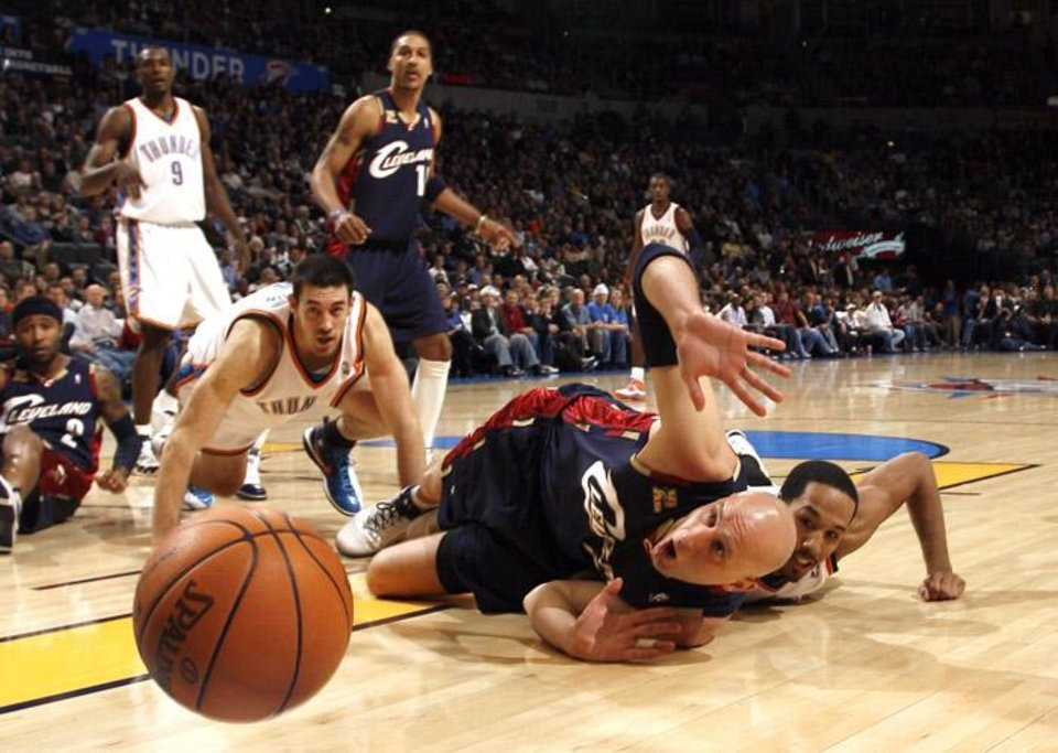 Cleveland's Zydrunas Ilgauskas (11) and Oklahoma City's Shaun Livingston (14) and Nick Collison (4) fight for a loose ball during the NBA basketball game between the Oklahoma City Thunder and the Cleveland Cavaliers, Sunday, Dec. 13, 2009, at the Ford Center in Oklahoma City. Photo by Sarah Phipps, The Oklahoman ORG XMIT: KOD