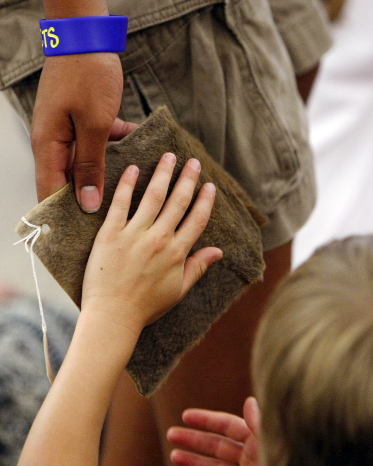 A child touches a piece of kangaroo skin during the Awesome Australia program Monday night at the Choctaw Library. Two more Australia-themed programs are planned for this month at metro libraries.