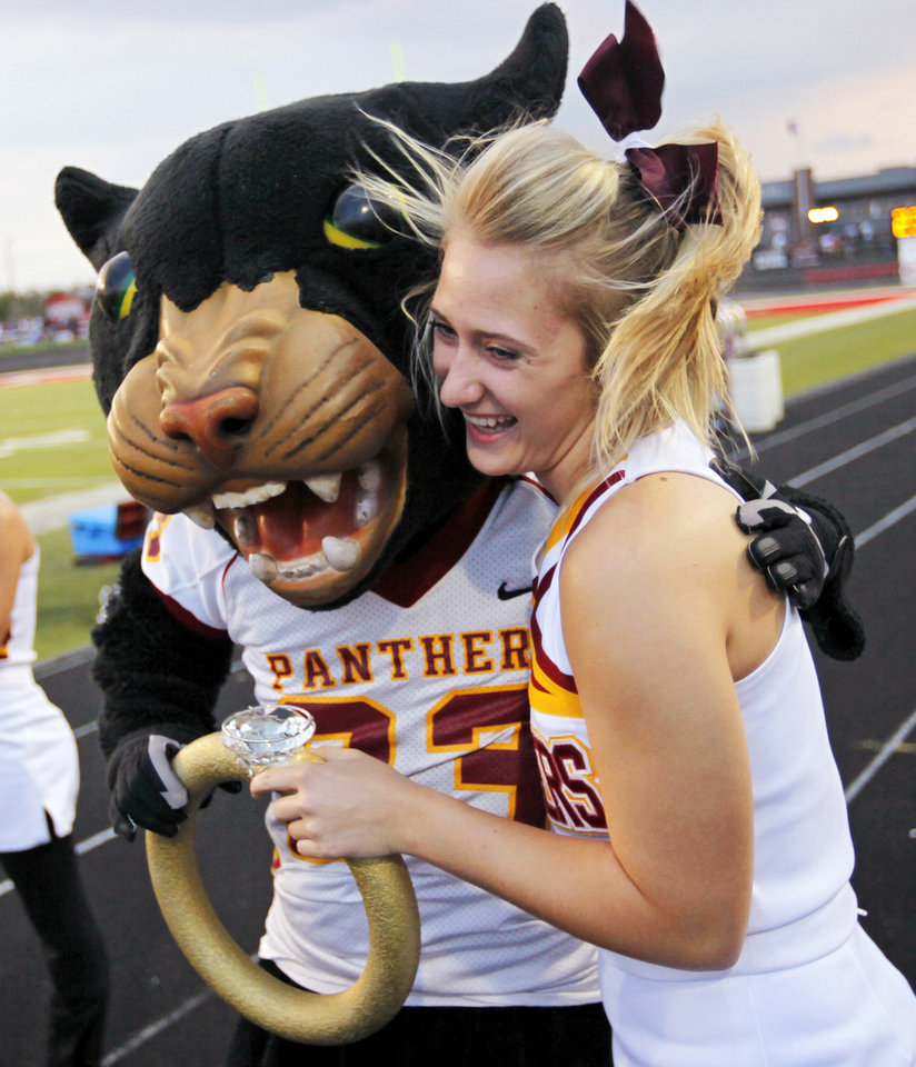 Photo - Putnam City North cheerleader Korbi Wood laughs as the PC North Panther gives her an oversized fake engagment ring during a high school football game between Mustang and Putnam City North in Mustang, Okla., Friday, Sept. 7, 2012. Photo by Nate Billings, The Oklahoman