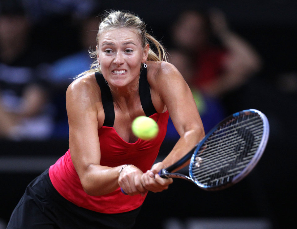 Russia's Maria Sharapova hits a backhand against Australian Samantha Stosur during their quarterfinal match at the Porsche tennis Grand Prix in Stuttgart, Germany, Friday, April 27, 2012.  (AP Photo/Michael Probst) ORG XMIT: PSTU122