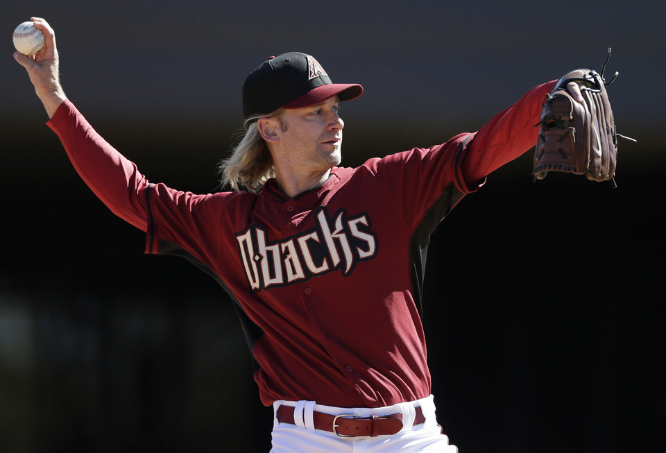 Photo - Arizona Diamondbacks pitcher Bronson Arroyo throws during baseball spring training, Wednesday, Feb. 12, 2014, in Scottsdale, Ariz. The Diamondbacks made the signing of Arroyo official Wednesday, five days after the two-year, $23.5 million deal was widely reported. (AP Photo/Gregory Bull)