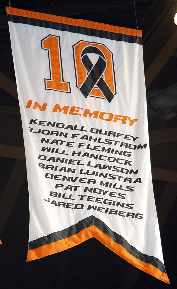 Photo - The banner for the ten members of the Oklahoma State men's basketball team that were killed in a 2002 plane crash hangs during the memorial service for Oklahoma State head basketball coach Kurt Budke and assistant coach Miranda Serna at Gallagher-Iba Arena on Monday, Nov. 21, 2011 in Stillwater, Okla. The two were killed in a plane crash along with former state senator Olin Branstetter and his wife Paula while on a recruiting trip in central Arkansas last Thursday. Photo by Chris Landsberger, The Oklahoman