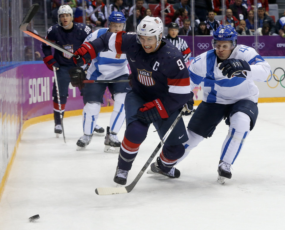 Photo - USA forward Zach Parise and Finland defenseman Kimmo Timonen vie for the puck during the first period of the men's bronze medal ice hockey game at the 2014 Winter Olympics, Saturday, Feb. 22, 2014, in Sochi, Russia. (AP Photo/Mark Humphrey)