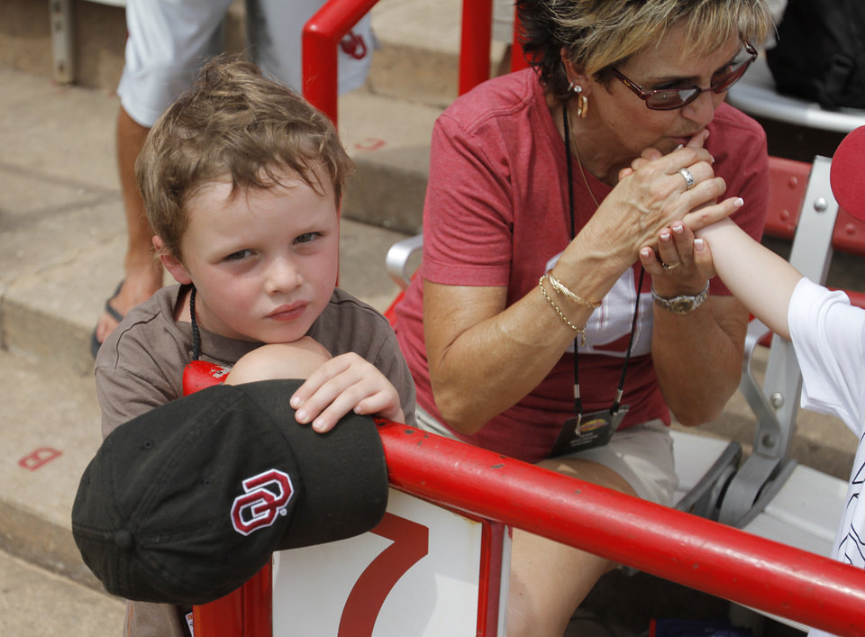 Gianni Lombardi, son of coach Melyssa Lombardi, waits for a game between OU and Arizona State to start during a Women's College World Series game at ASA Hall of Fame Stadium in Oklahoma City, Sunday, June 3, 2012.  Photo by Garett Fisbeck, The Oklahoman