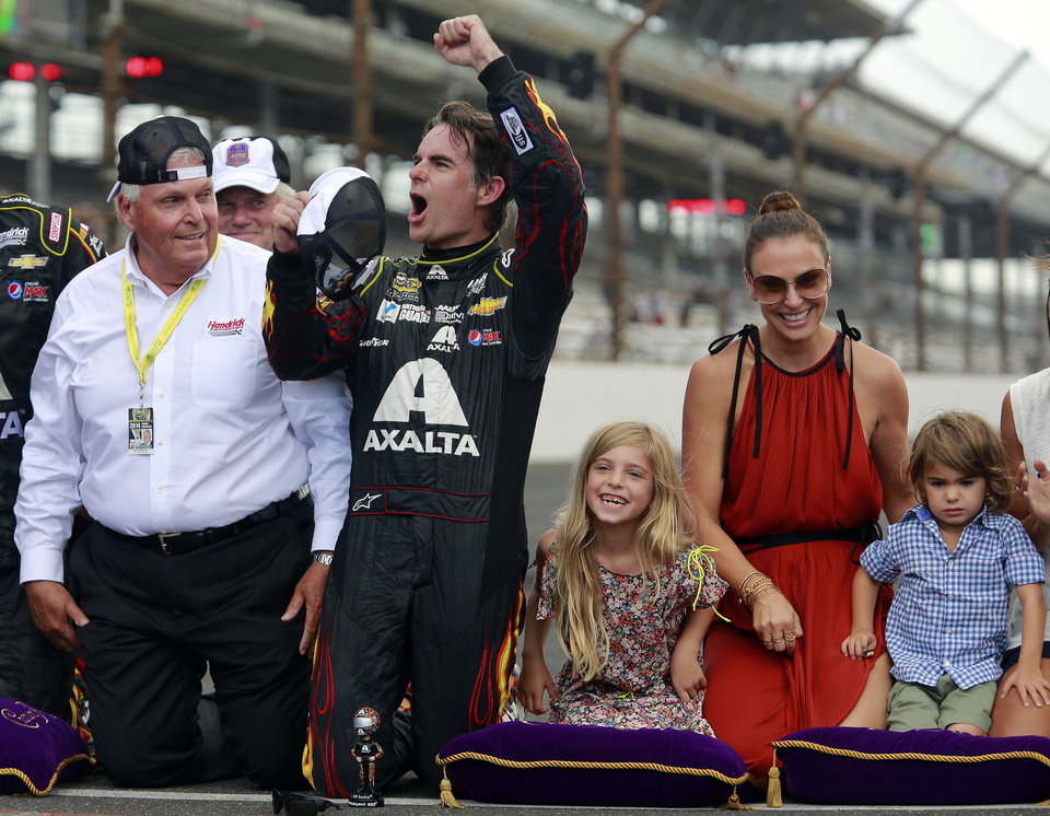 Photo - Jeff Gordon celebrates after winning the NASCAR Brickyard 400 auto race at Indianapolis Motor Speedway in Indianapolis, Sunday, July 27, 2014. At left is team owner Rick Hendrick. At right are Gordon's wife, Ingrid Vandebosch, and their children, Ella Sofia and Leo Benjamin. (AP Photo/R Brent Smith)