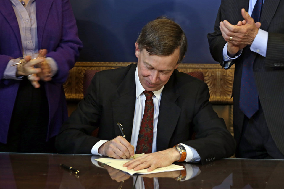 Photo - Colorado Gov. John Hickenlooper is applauded by lawmakers as he signs the state's gun control bill into law at the Capitol in Denver on Wednesday, March 20, 2013. (AP Photo/Ed Andrieski, Pool)