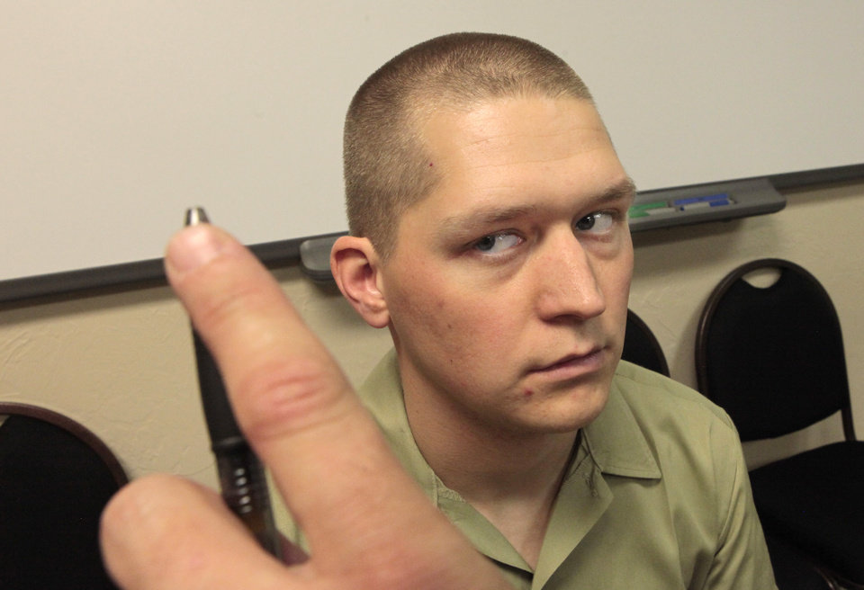 Photo -      Oklahoma Highway Patrol cadet Kaleb Kemp follows a pen with his eyes held by cadet Ryan Lon, as an example of a field test for drugs. Photo by David McDaniel, The Oklahoman   David McDaniel -
