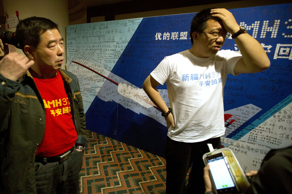 Photo - Steve Wang, right, a representative from the committee for relatives of Chinese passengers onboard the missing Malaysia Airlines Flight 370 talks to journalists after a closed door meeting with Malaysian officials via teleconference in Beijing, China, Wednesday, April 2, 2014.  A Malaysian police investigation into the pilots of the missing Malaysian jet might turn up nothing, the force's chief said Wednesday, while the head of the international search effort also acknowledged that an air hunt to spot wreckage on the surface of the southern Indian Ocean was not certain of success. The Chinese writing on the t-shirts read