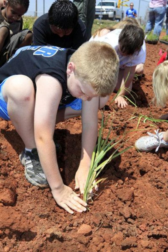 Third-grader Baxter Beavers, 9, plants a lake sedge in the outdoor classroom and wetlands at Deer Creek Grove Valley Elementary School. PHOTO BY PAUL B. SOUTHERLAND, THE OKLAHOMAN <strong>PAUL B. SOUTHERLAND - PAUL B. SOUTHERLAND</strong>