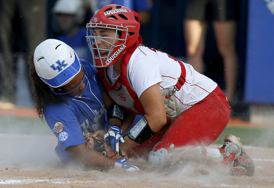 Photo - La.-Lafayette's Lexie Elkins (33) tags out Kentucky's Darington Richardson (43) at home in the fifth inning of a Women's College World Series game between La.-Lafayette and Kentucky at ASA Hall of Fame Stadium in Oklahoma City Thursday, May 29, 2014. Photo by Bryan Terry, The Oklahoman